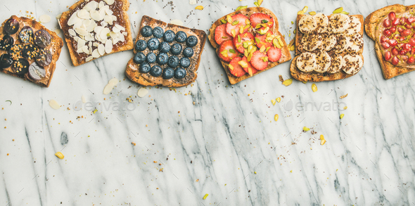 Vegan whole grain toasts with fruit, seeds, nuts, copy space - Stock Photo - Images