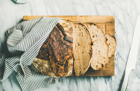 Flat-lay of freshly baked sourdough bread cut into pieces - Stock Photo - Images