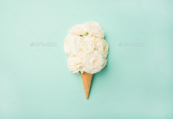 Waffle cone with white buttercup flowers over blue pastel background - Stock Photo - Images