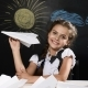 School Concept. Attractive Girl Sit with Paper Plane in Hand. Desk and Blackboard Behind Them - VideoHive Item for Sale
