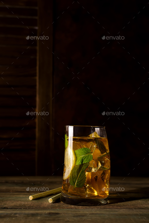 cocktail glass with ice, mint and ginger on a dark wooden backgorund - Stock Photo - Images
