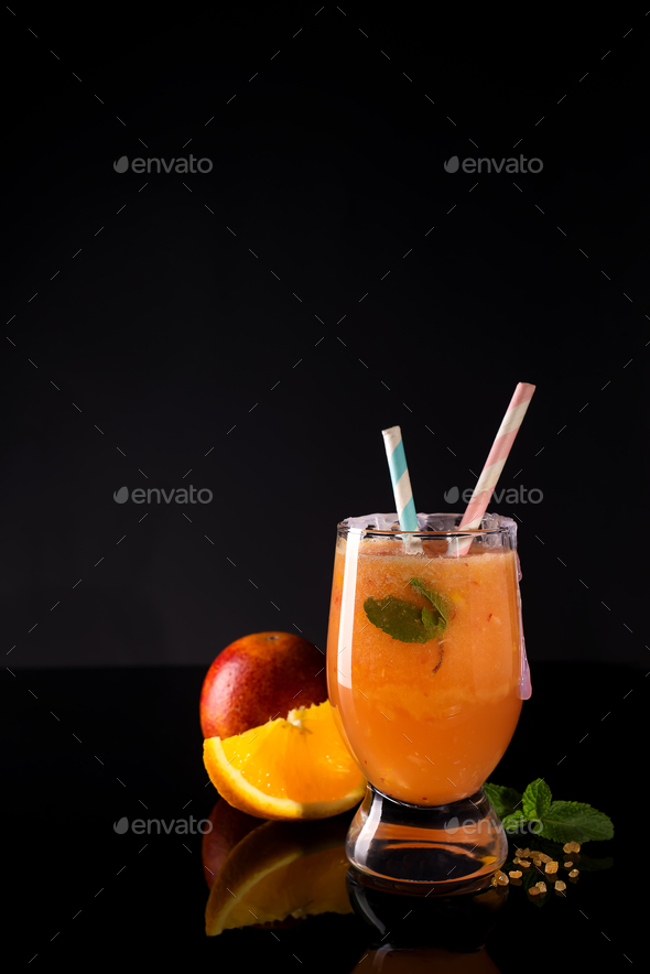 Paloma cocktail with fresh grapefruit, orange and mint on a black glass background - Stock Photo - Images