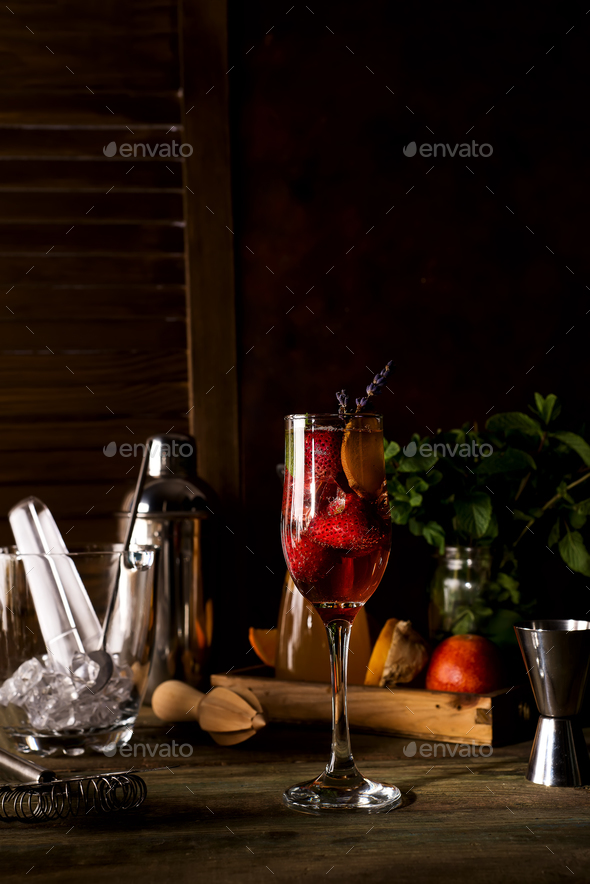 Champagne with slices of strawberry and lavender twigs on dark wooden backgorund - Stock Photo - Images