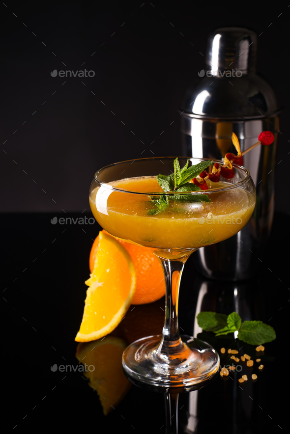 Frozen cocktail smoothie Margarita with brownish sugar and mint on a black glass background - Stock Photo - Images
