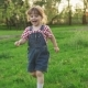 Happy Little Girl Running on Green Grass at Sunset in Sunny Summer Day - VideoHive Item for Sale