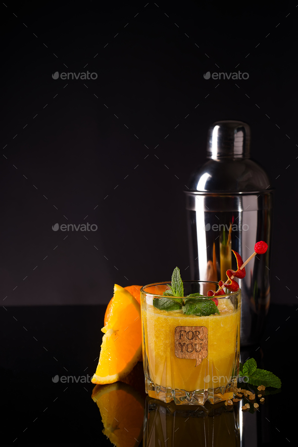 Fresh cocktail with orange, mint and ice on dark wooden backgorund - Stock Photo - Images