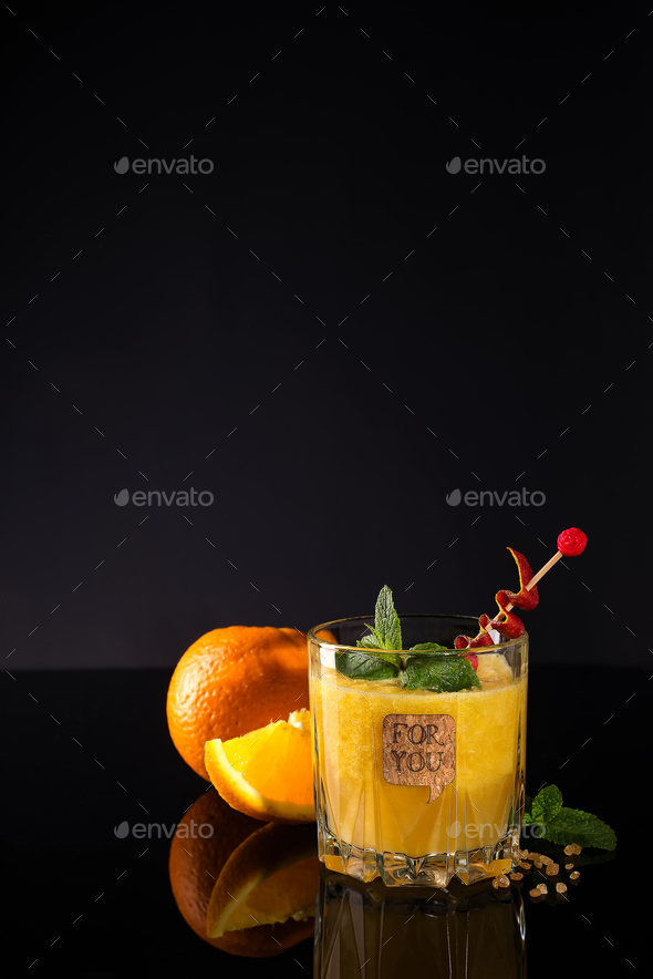 Fresh cocktail with orange, mint and ice on black glass backgorund, copy space - Stock Photo - Images