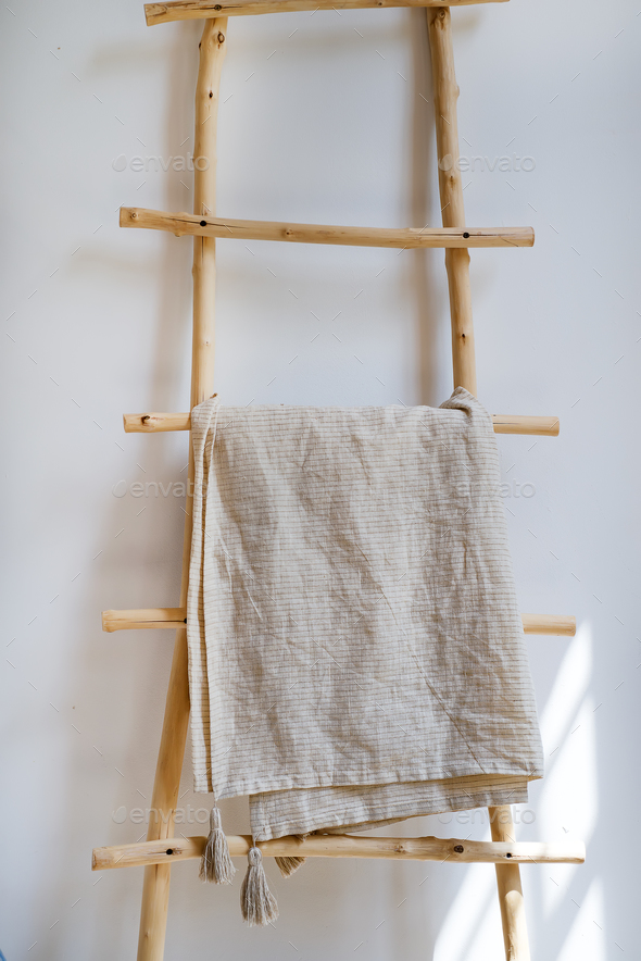 Tablecloth textile on wooden hanger in the background a white wall - Stock Photo - Images