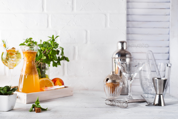 lemonade in the decanter on a wooden tray and Cocktail shaker for preparing a summer cocktail - Stock Photo - Images