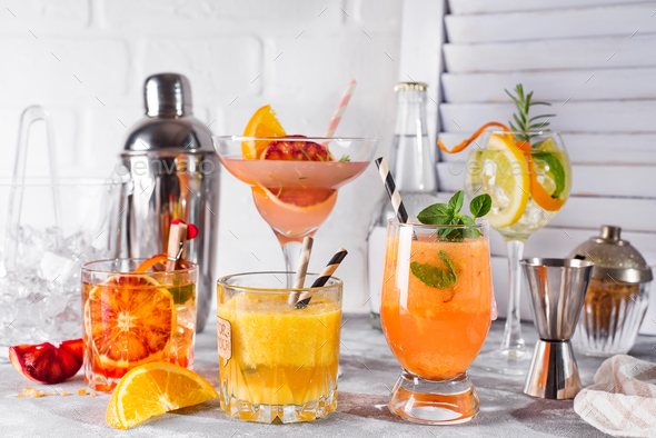 Set of classic cocktails of gin tonic with orange, with lime and mint leaves in glasses  - Stock Photo - Images
