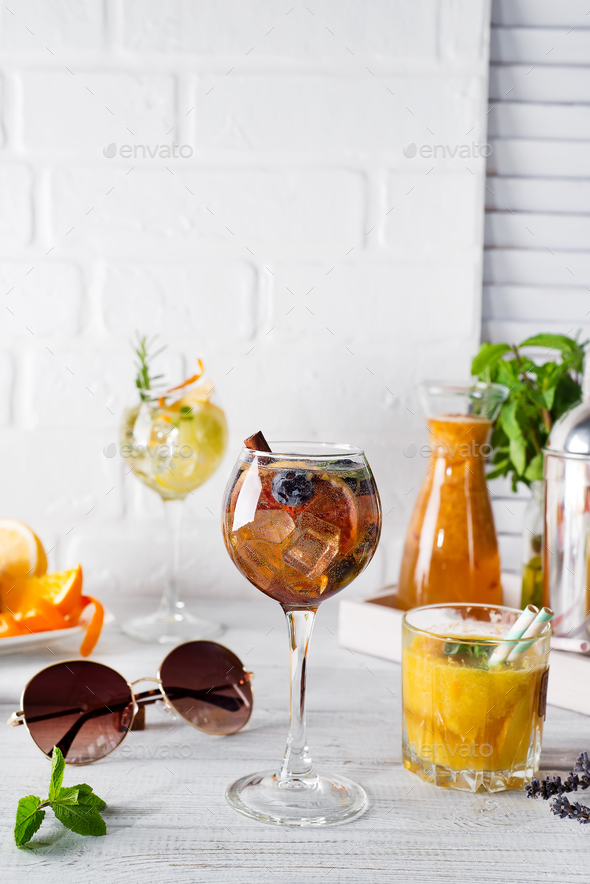 glass of cocktail with cinnamon, berries and brown sugar and a glass with an orange cocktail - Stock Photo - Images