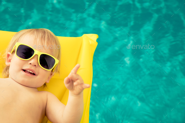 Funny baby boy in swimming pool - Stock Photo - Images
