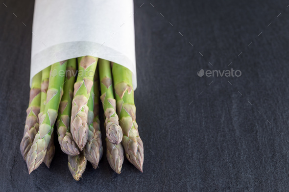 Bunch of fresh green asparagus on dark slate background with cop - Stock Photo - Images