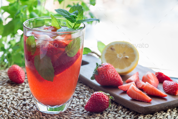 Glass of refreshing iced tea with strawberries and mint, horizon - Stock Photo - Images
