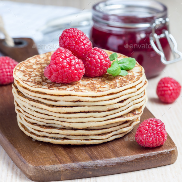 Stack of pancakes or fritters with raspberry on wooden board, ra - Stock Photo - Images