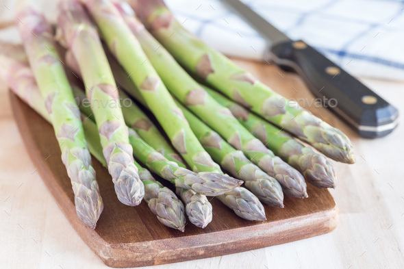 Bunch of fresh green asparagus on a wooden board, horizontal - Stock Photo - Images