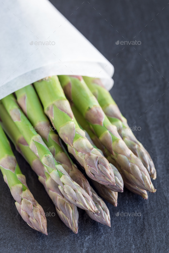 Bunch of fresh green asparagus on a dark slate background, verti - Stock Photo - Images