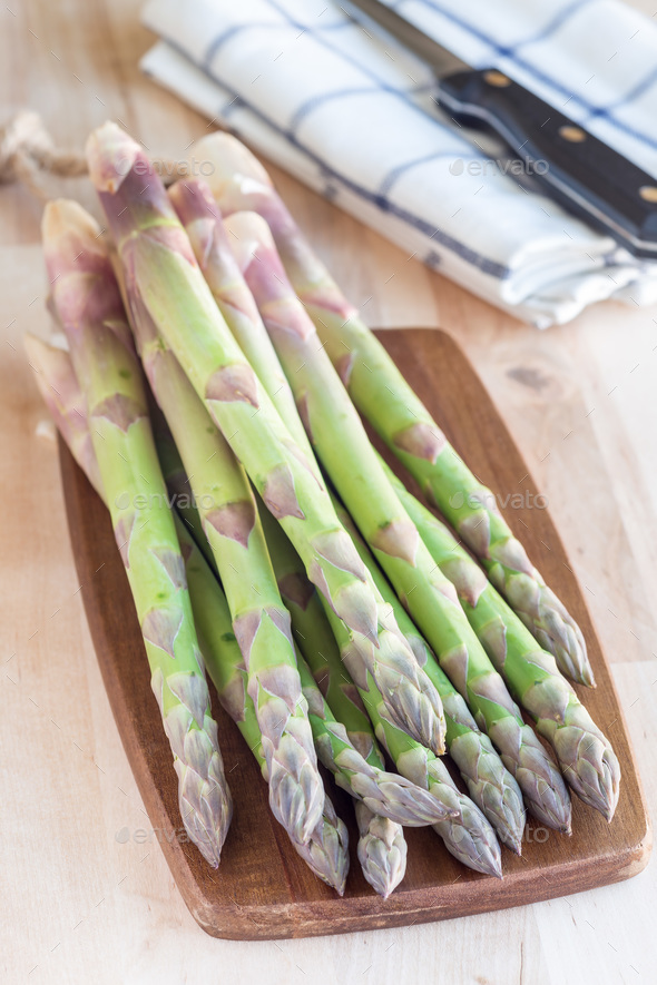 Bunch of fresh green asparagus on wooden board, vertical - Stock Photo - Images