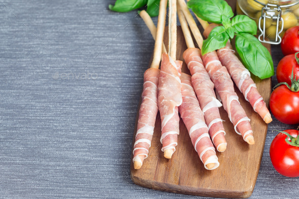 Grissini bread sticks coiled with prosciutto ham on wooden board - Stock Photo - Images