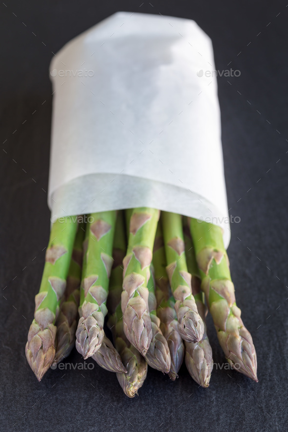 Bunch of fresh green asparagus on dark slate background, vertica - Stock Photo - Images