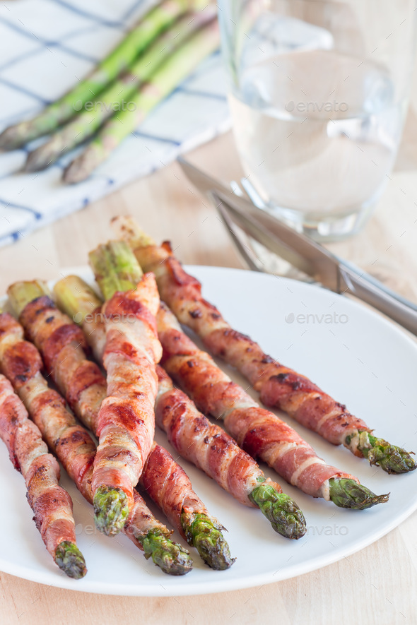 Healthy appetizer, green asparagus wrapped with bacon on a white - Stock Photo - Images
