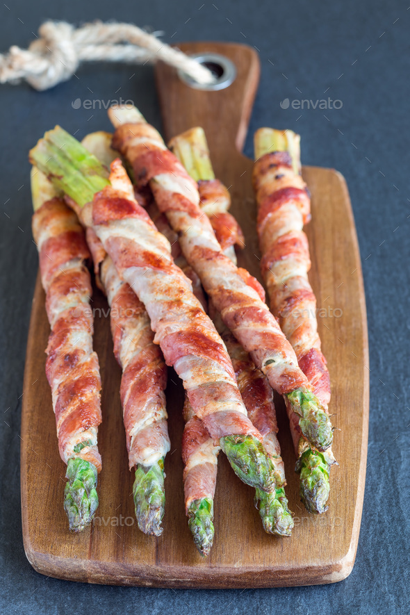 Healthy appetizer, green asparagus wrapped with bacon on a woode - Stock Photo - Images