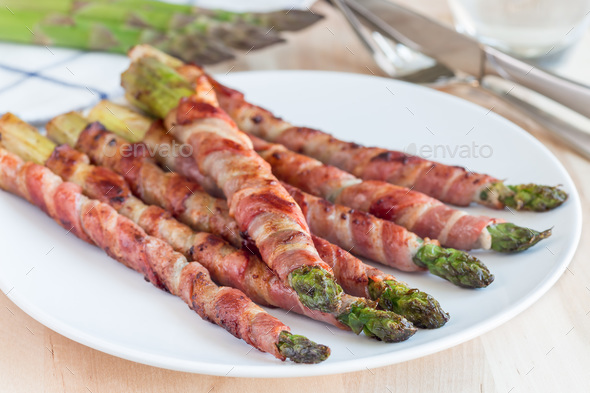 Healthy appetizer, green asparagus wrapped with bacon on white p - Stock Photo - Images