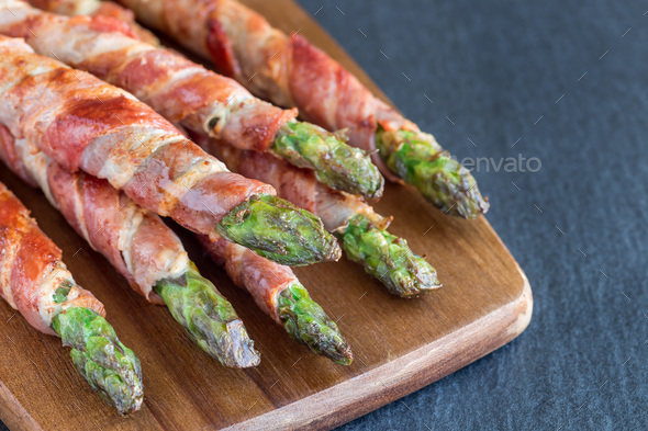 Healthy appetizer, green asparagus wrapped with bacon on wooden - Stock Photo - Images