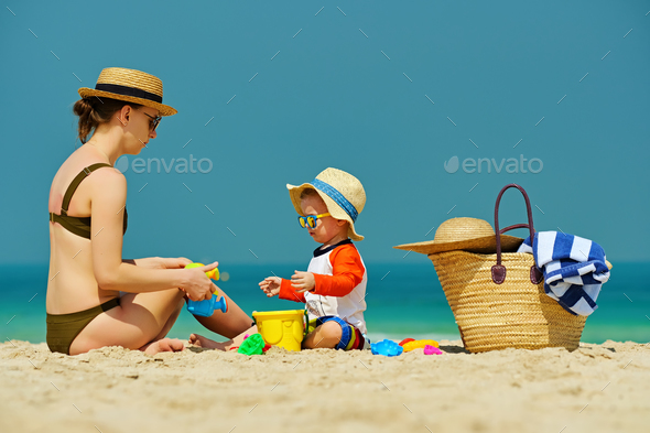 Toddler boy playing with mother on beach - Stock Photo - Images