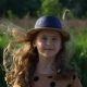 A Joyful Child in a Summer Hat Looks Into the Camera in Windy Weather - VideoHive Item for Sale