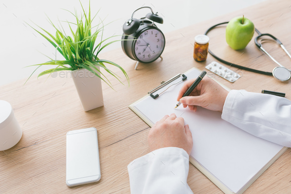 Female doctor writing notes on clipboard paper during medical ex - Stock Photo - Images