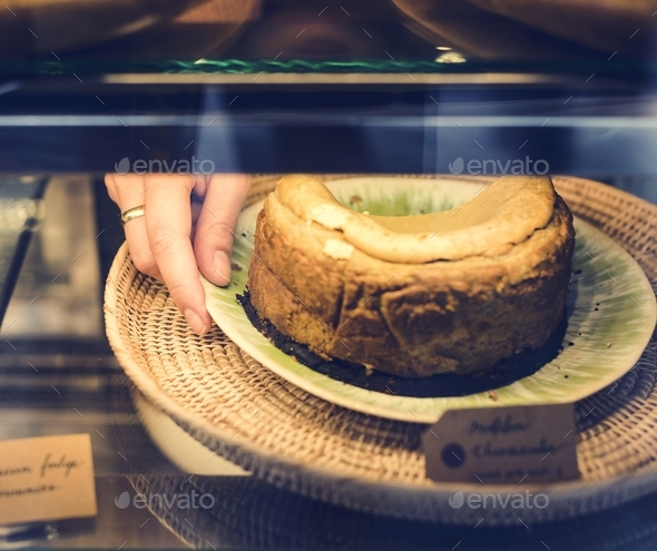 Woman getting cake out of the display fridge - Stock Photo - Images