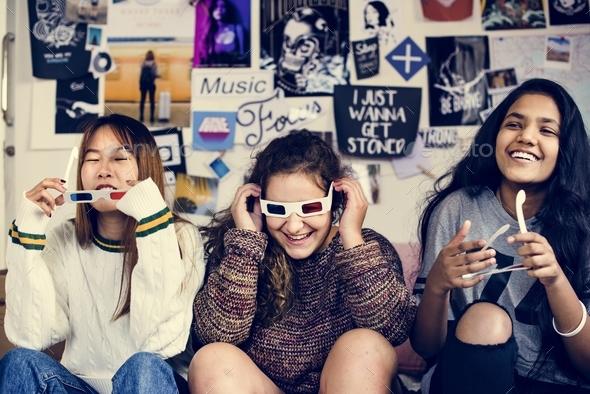 Teenage girls wearing 3d movie eyeglasses enjoying laughing and watching TV - Stock Photo - Images