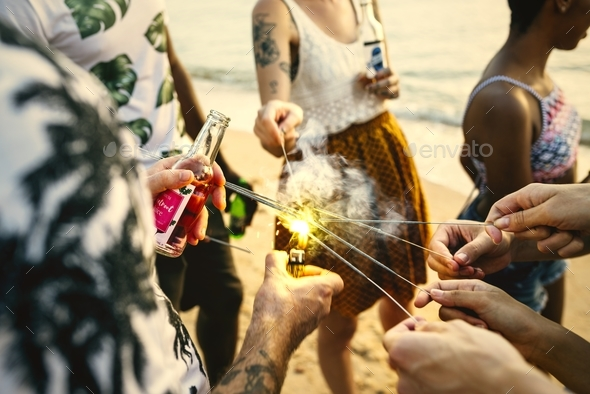 A diverse group of friends enjoying sparklers at the beach toget - Stock Photo - Images