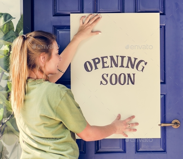 Woman putting on store opening soon sign - Stock Photo - Images