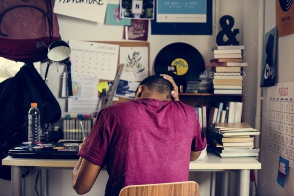 Teenage boy in a bedroom doing work stressed out and frustrated - Stock Photo - Images