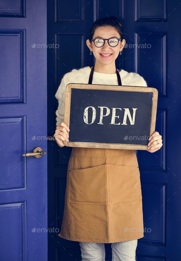 A cheerful small business owner with open sign - Stock Photo - Images