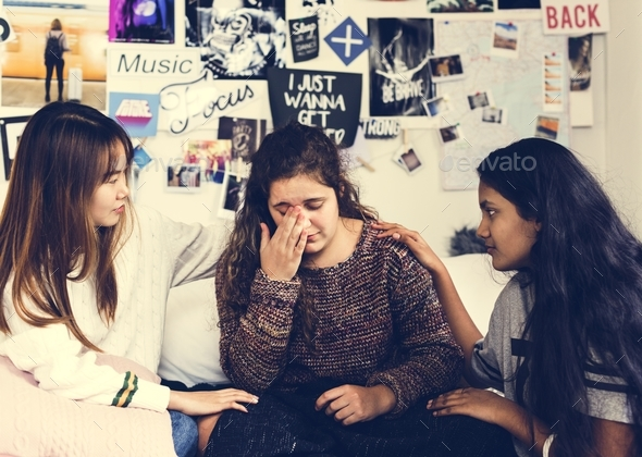 Teenage girls consoling their depressed crying troubled friend - Stock Photo - Images