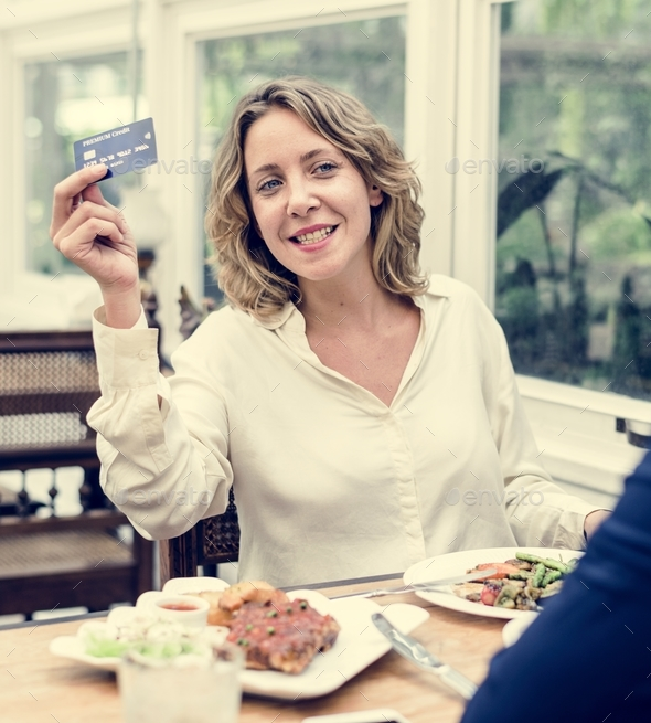 Woman paying lunch with credit card at restaurant - Stock Photo - Images