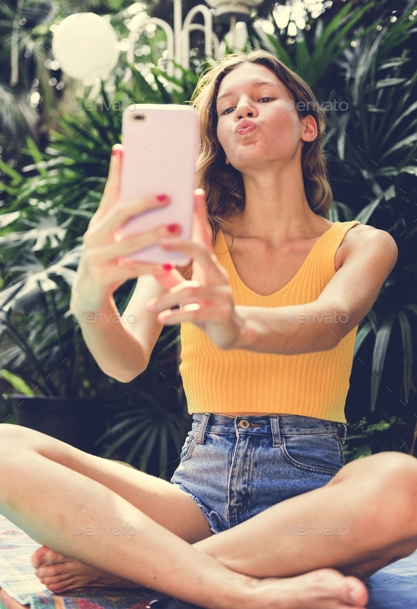 Girl taking a selfie in summertime - Stock Photo - Images