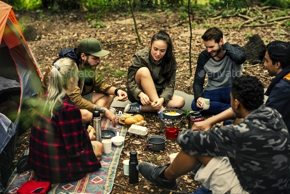 Friends camping in the forest together - Stock Photo - Images