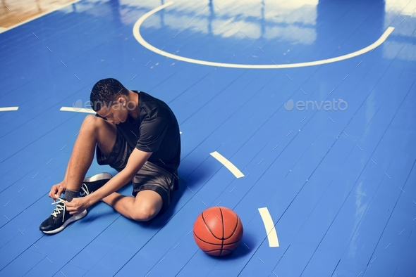 African American teenage boy tying his shoe laces on a basketball court - Stock Photo - Images
