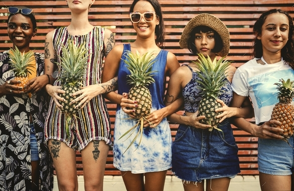 A diverse group of women standing and holding pineapple together - Stock Photo - Images