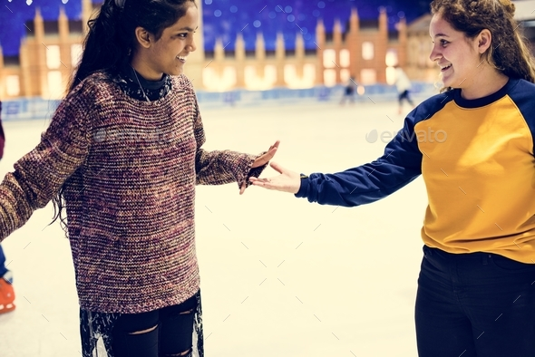 Girl friends playing ice skate together - Stock Photo - Images