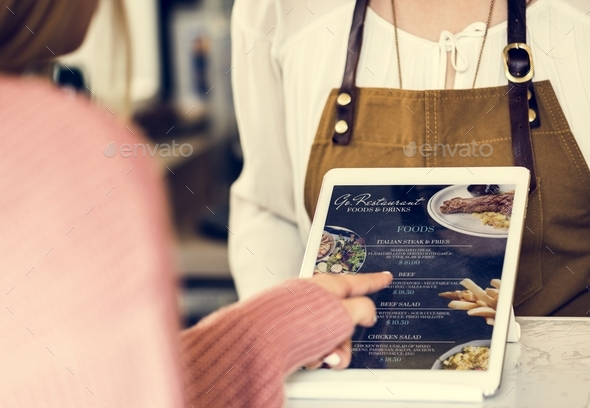 Customer ordering food at restaurant counter - Stock Photo - Images