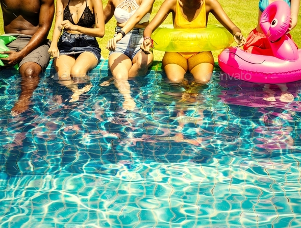 A diverse group of friends enjoying summer time by the pool with - Stock Photo - Images