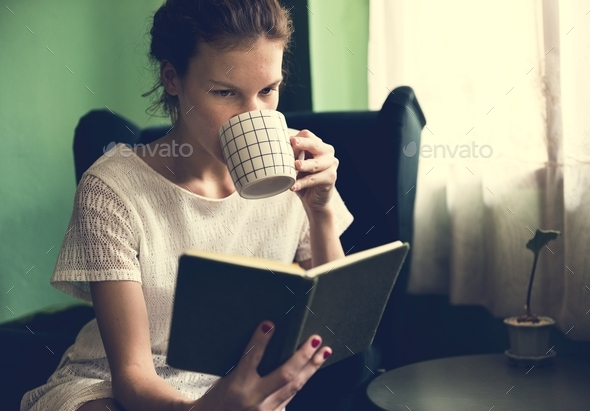 Girl reading a book at home - Stock Photo - Images