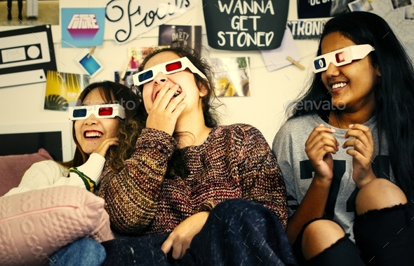 Teenage girls wearing 3d movie eyeglasses enjoying laughing and - Stock Photo - Images