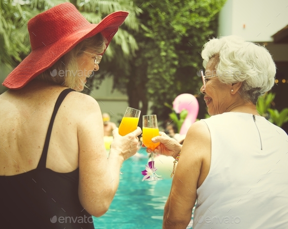 Senior couple women with orange juice by the pool together - Stock Photo - Images