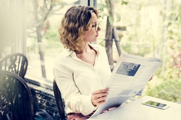 Business woman reading newspaper in the morning - Stock Photo - Images